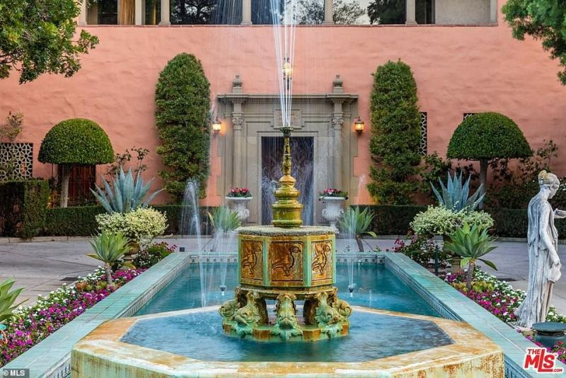 The property has several fountains surrounded by lush greenery and bright flowers, including one in the driveway