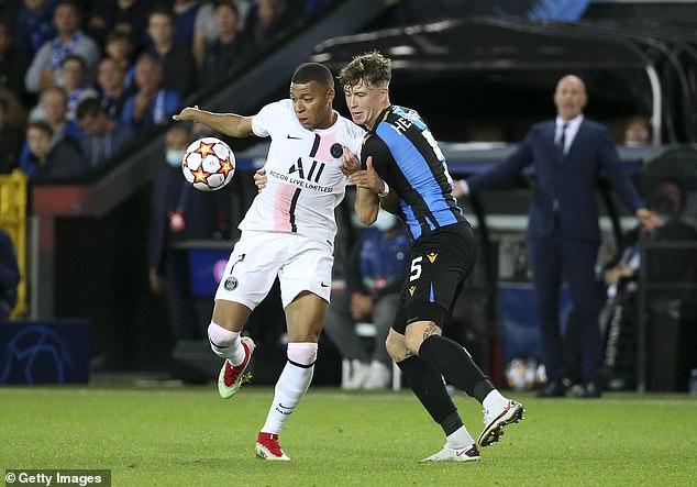 Club Bruges defender Jack Hendry grapples with PSG forward Kylian Mbappe