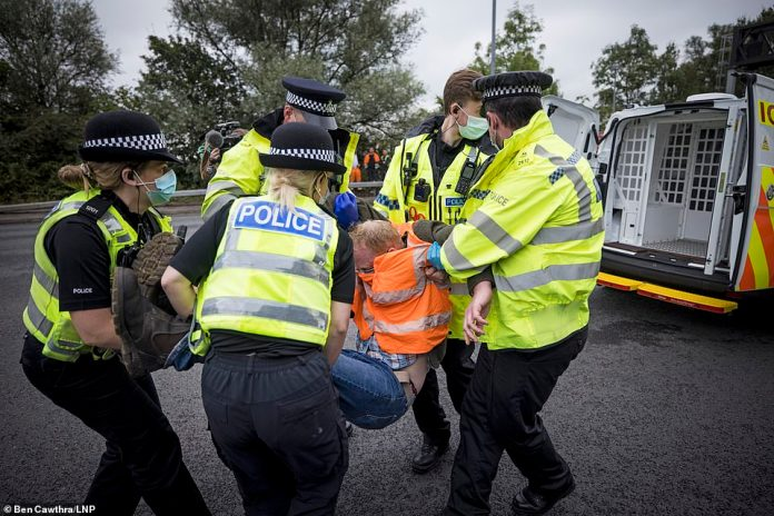 Police arrest a climate change demonstrator blocking theM25 at Junction 23 for the A1 this morning