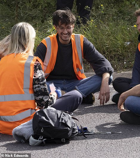 A giggling protester laughs as he sits on the road at junction 3 of the M25 in Swanley, Kent, on Monday, before he is pictured again in a red jacket near a Dartford Crossing roundabout on Wednesday