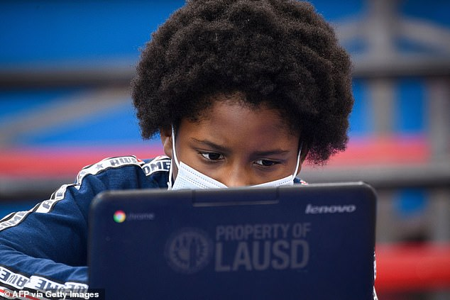 The study found that increased screen time for many children during the pandemic due to virtual learning and less outdoor activities has had a negative impact on their eye health.  Pictured: A student in Los Angeles, California attends virtual classes in February