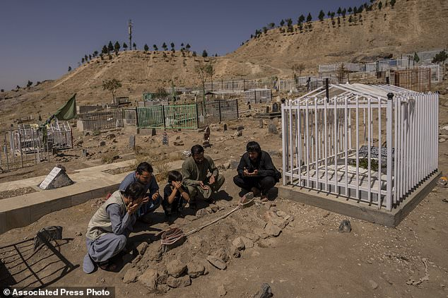 The Ahmadi family pray at the cemetery next to family graves of the family members killed