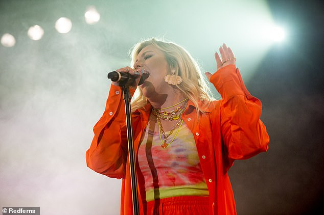 Wow!  The 25-year-old This Is Real songstress wore a '90s-style tie-dye cami top, which she paired with a bold orange shirt-jacket and matching joggers.