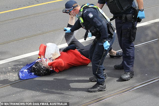 The woman was bowled over by the two cops before they fired pepper spray directly on to her face as she lay defenceless on the road grabbing her eyes