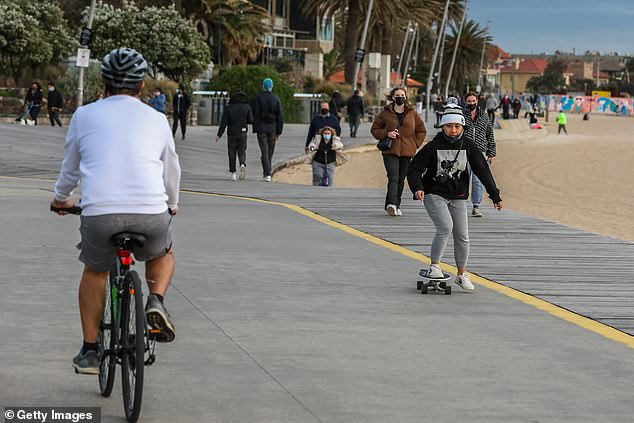 Victorians will finally be released from the current strict restrictions on October 26 to coincide with when the state hits 70 per cent double-dose vaccination (pictured, St Kilda on Sunday)