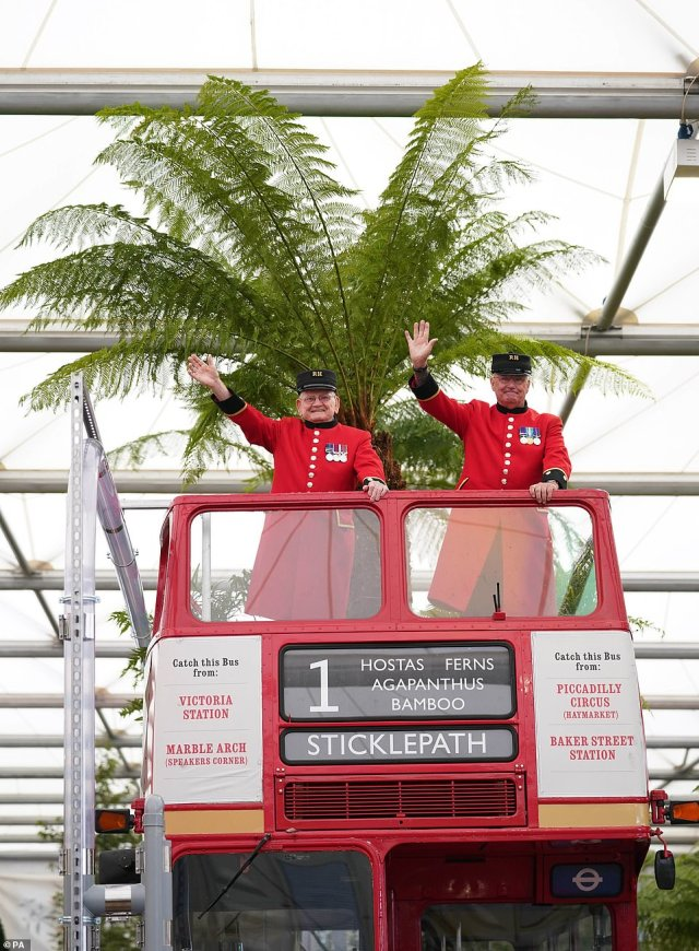 Chelsea Pensioners in uniform wave from the top of a repurposed double-decker bus in the Bowdens garden hosting bamboo shoots and ferns