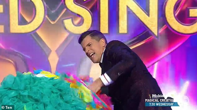 Some help please! Prior to being revealed, Lote had some trouble getting his masked off, with host Osher Gunsberg (pictured) stepping in to hoist it off
