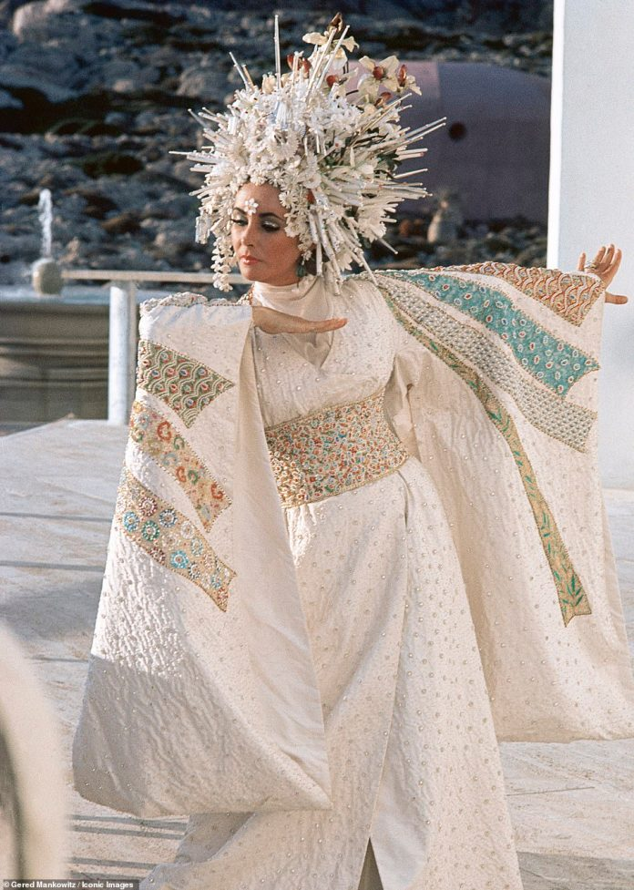 Taylor strikes a pose in her extravagant outfit;  Starr played wealthy socialite Flora 'Sissy' Goforth, who lived in an island paradise with a string of servants