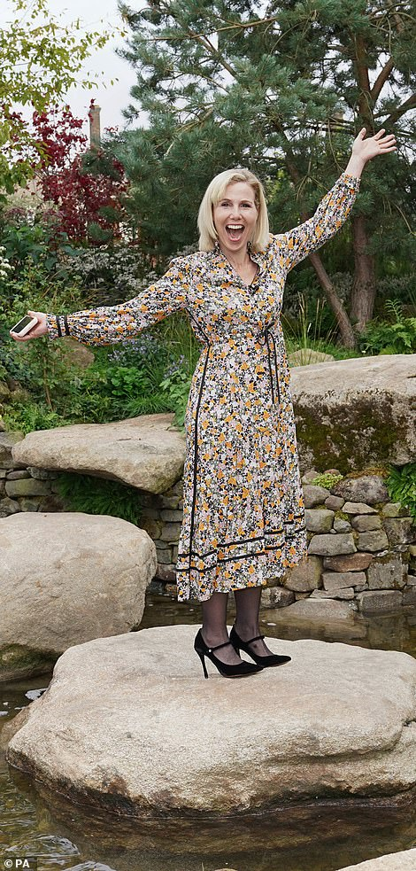 Sally Phillips, wearing a floral dress, stood in the middle of the Psalm 23 garden's pond