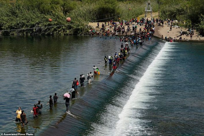 Haitian migrants use a dam to cross into the United States from Mexico on Saturday
