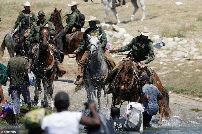 U.S. border patrol officers on horseback prevent migrants from reaching the U.s. as they try to return to their camp after having crossed from the U.S. into Mexico to buy food on Sunday