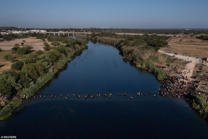 Migrants streamed back across the Rio Grande River from Del Rio, Teas to Acuna, Mexico using a rope to guide them across the water