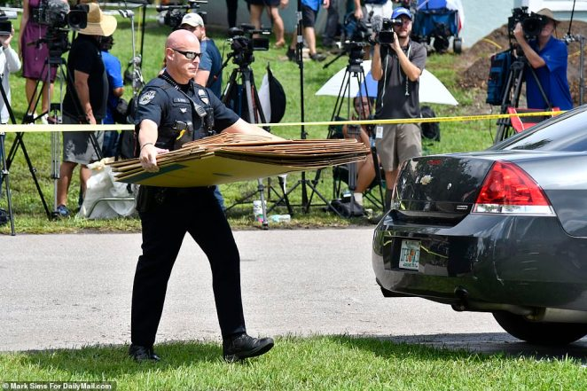 One officer was seen carrying boxes into the home as they searched for evidence