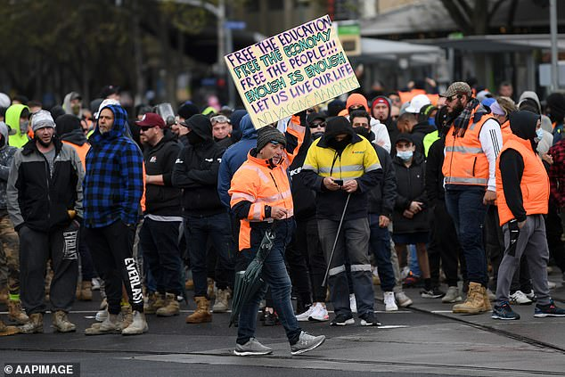 A man in hi-vis is pictured holding a sign that reads 'let us live our life - no vaccine mandate'