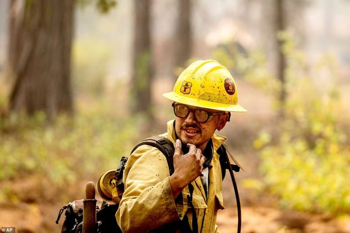 A firefighter mops up hot spots in the Trail of 100 Giants grove of Sequoia National Forest on Monday