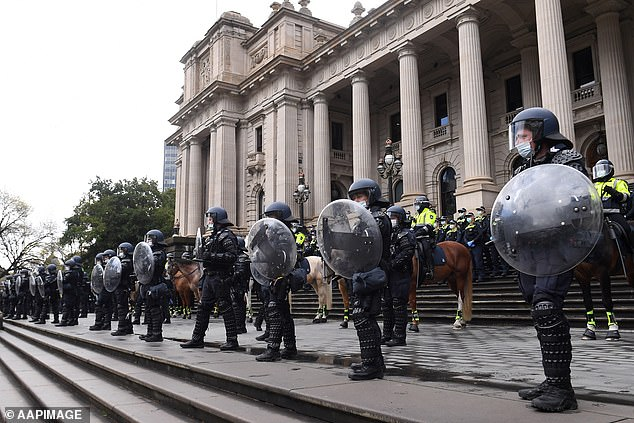 Riot police are seen outside the Victoria's Parliament House during Tuesday's protest, which came a day after violent demonstrators damaged the CFMEU head office in Melbourne's CBD