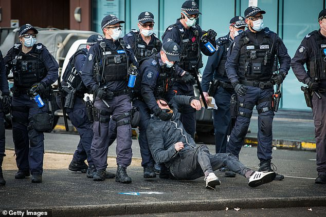 Police detain a man during a protest at the CFMEU headquarters on September 20
