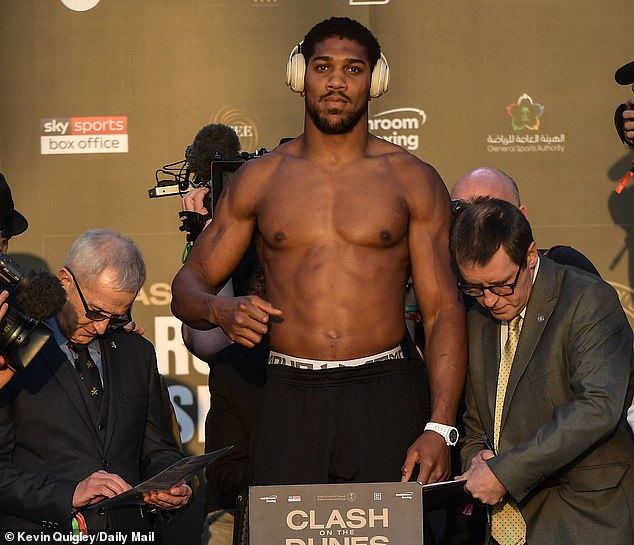 Joshua shows off his physique atop the scales on Friday
