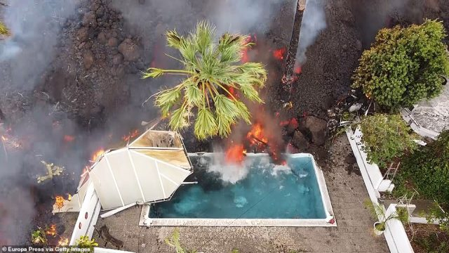Lava inches its way into the pool of a house on La Palma, having already demolished a nearby building. In total, 166 homes have now been destroyed by the eruption