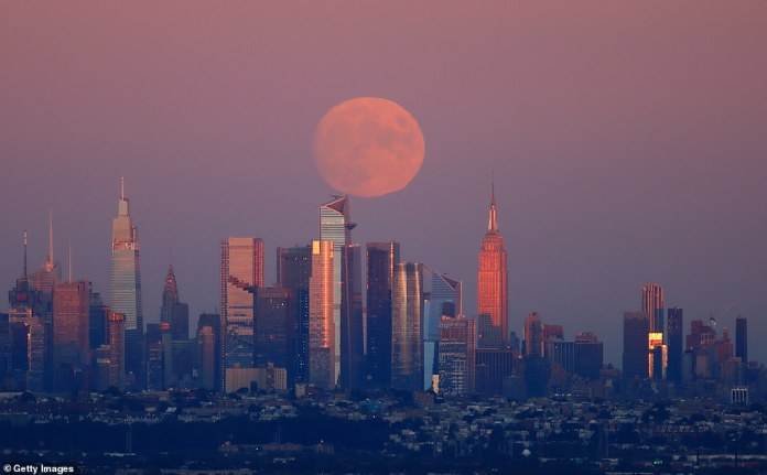Harvest Moon rises behind Manhattan, One Vanderbilt, Chrysler Building, Spiral, Hudson Yards and Empire State Building as the sun sets in New York City