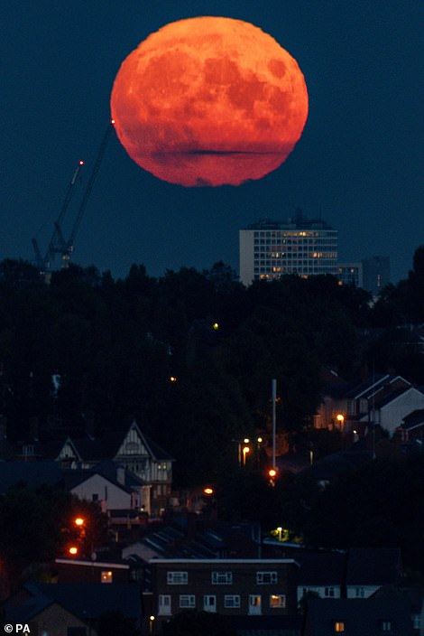 The full moon, also known as the harvest moon, rises over Birmingham
