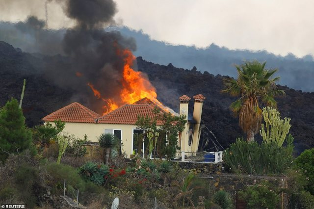 A huge lava flow (rear, in black) sets light to a house as it demolishes the building in theLos Campitos area of La Palma