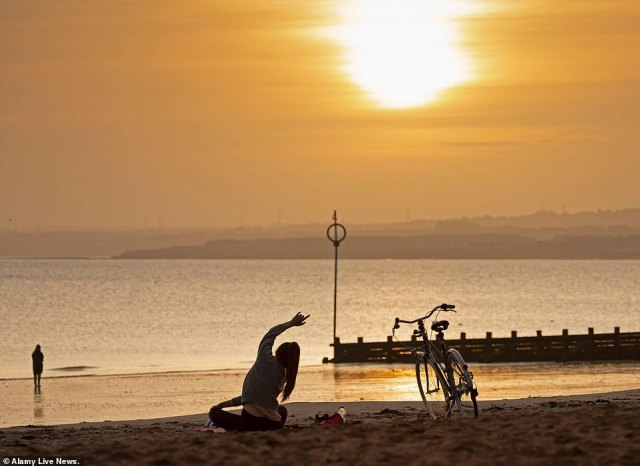 A young female cyclist takes yoga exercise on the sandy beach just after sunrise by the Firth of Forth, Portobello, Edinburgh, Scotland, on the last day of summer