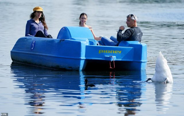Visitors travel by pedalo along the Serpentine, Hyde Park, London, where temperatures have peaked at 73F (23C) today, with bright spells of sunshine