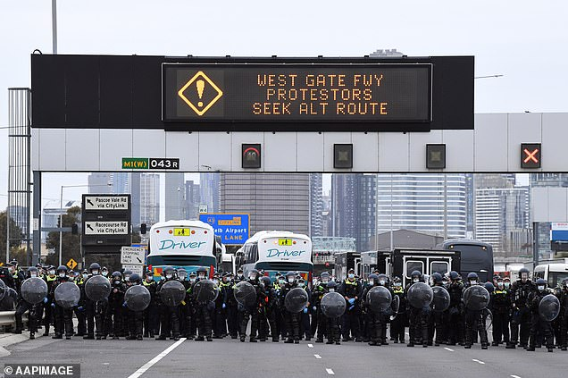 Riot police officers form a wall as they wait for protesting construction workers on the West Gate Bridge on Tuesday afternoon
