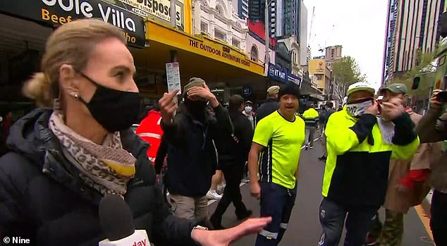 'Look we're not going to be intimidated':A group of men clad in fluorescent-yellow vests started to heckle the reporter, forcing her to apologise for their crude language