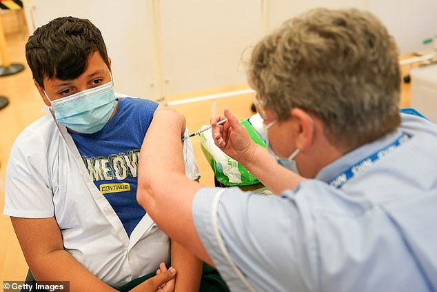 Felix Dima, 13, of Newcastle receives the Pfizer vaccine at the Excelsior Academy in Newcastle-on-Tyne