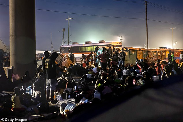 A bus to transport migrants to other parts of the US for processing is seen by the Del Rio bridge in Texas Tuesday night