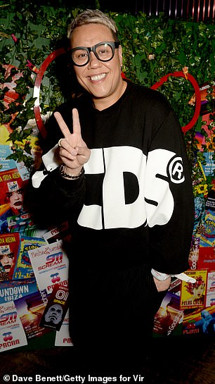 Fashion Forward: Gok Wan looked chic in an oversized black sweatshirt featuring a white text motif while he flashed a peace sign to photographers
