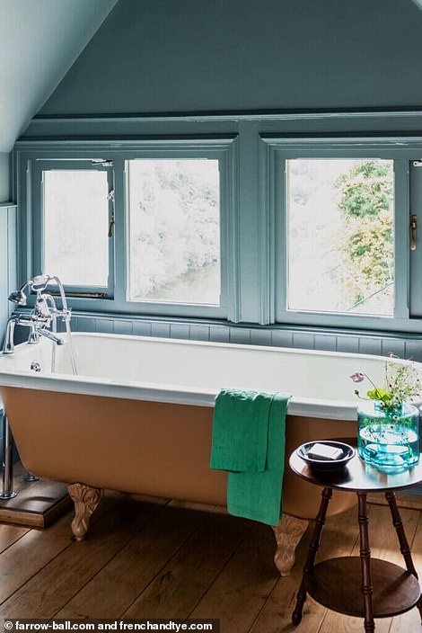 The bathroom features a gold stand-alone bath, parquet floors and a dusky blue wall color