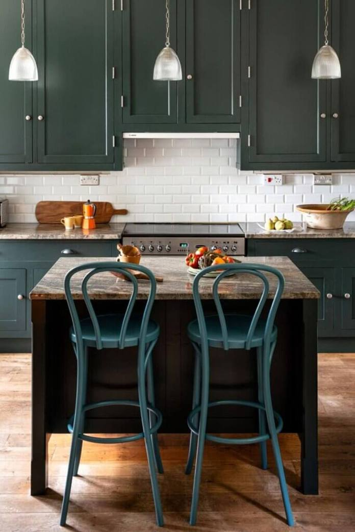 A kitchen in a moody indigo and a marble-topped island, to the point, antique lamps add style to the food preparation area