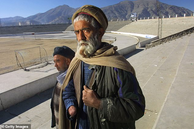 Abdul Jalil (R) and Mohammed Ismael stand inside Ghazi Stadium January 26, 2002 in Kabul, Afghanistan. Abdul lost his hand when the Taliban accused him of being a thief and cut it off as punishment