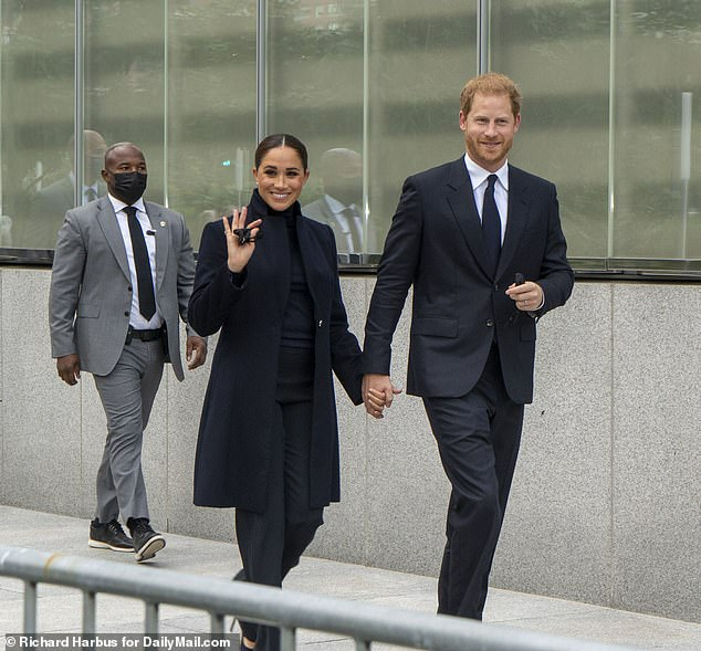 The mystery bodyguard (left) was dressed in a smart grey suit and black wingtips that had been resoled with comfortable sneaker soles
