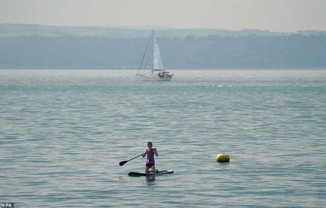 Temperatures are set to plunge from 21-22C (70-72F) over the weekend to just 14-16C (57-61F) by Wednesday. Pictured:A paddle boarder in the sea off of Southsea beach in Hampshire on Wednesday