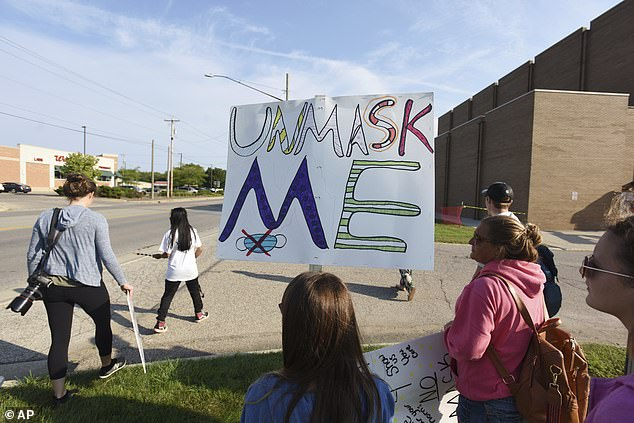 The mask mandates in schools have become a heated topic with protests across the nation. Pictured, protestors at Lakeshore High School, in Stevensville, Michigan on September 7.