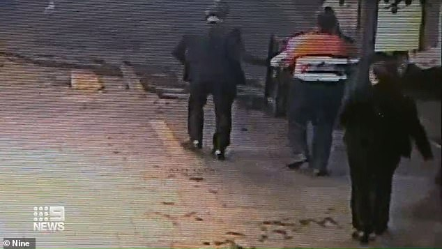 Fine proceed to get out of his truck, put on gloves and drag the body of the young man several metres away to a footpath. The truck driver is pictured being taken into custody