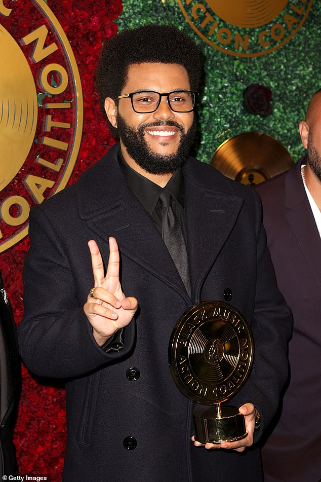 Nice to meet you: The Blinding Lights hitmaker beamed for onlookers while flashing a peace sign as he launched a sophisticated new look with a pair of black rimmed glasses