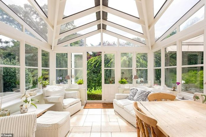 The period property features a large conservatory with a seating area and dining table, overlooking the landscaped gardens