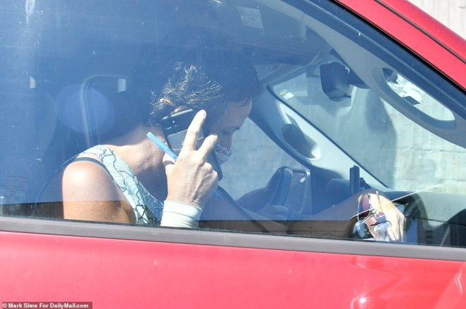 Roberta, pictured in the passenger seat, is seen talking on the phone as the couple drives away