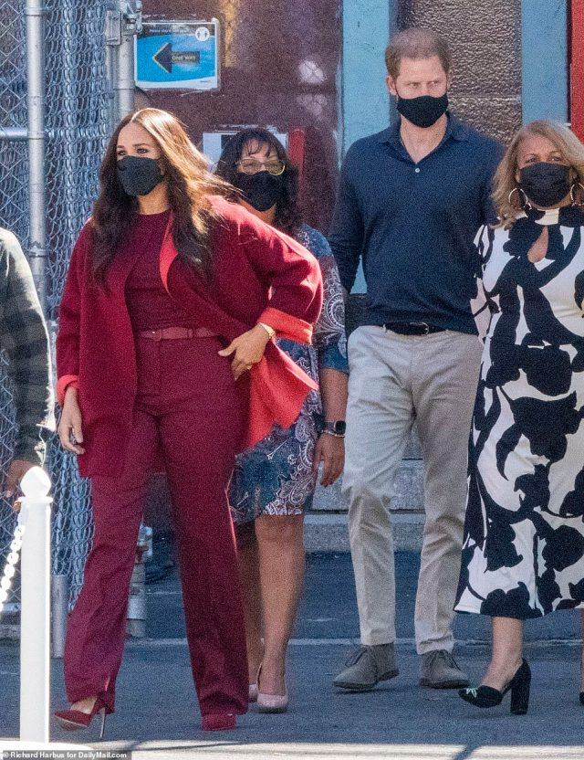 The couple sported matching black face masks as they greeted children in the playground of the public school