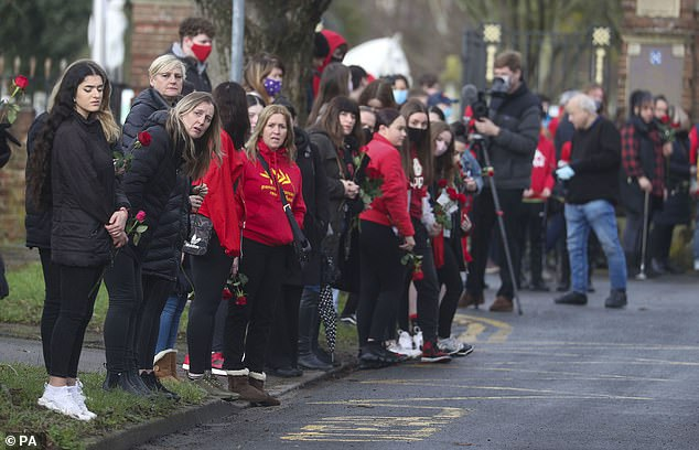 People watch the funeral procession of Olly Stephens as it slows at All Hallows Road