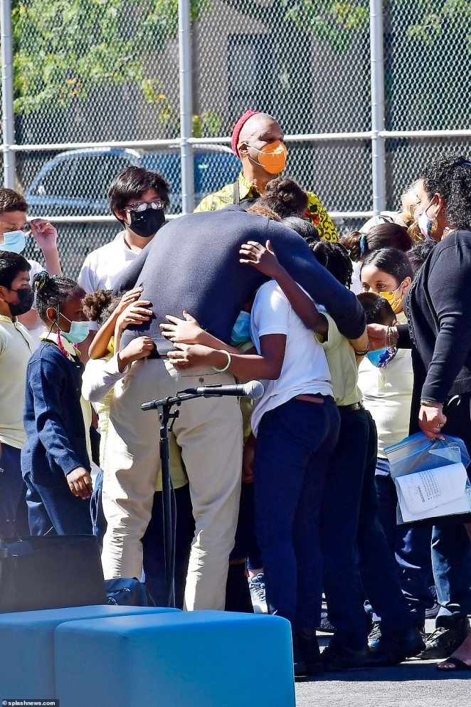 The prince is seen embracing a group of children at the school which issupported in part by nonprofit Graham Windham