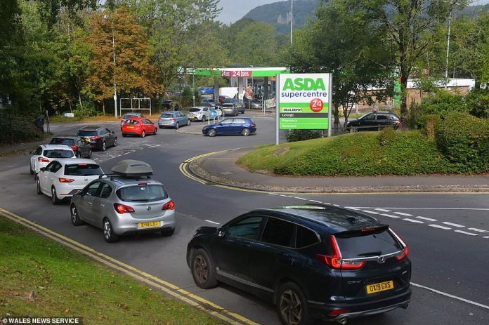 Drivers wait in line for fuel at a petrol station near the M4 in Coryton, Cardiff today as concerns grow