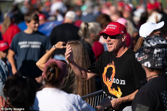 A man wearing a QAnon t-shirt waits in line for a rally featuring former President Donald Trump on Saturday in Perry, Georgia