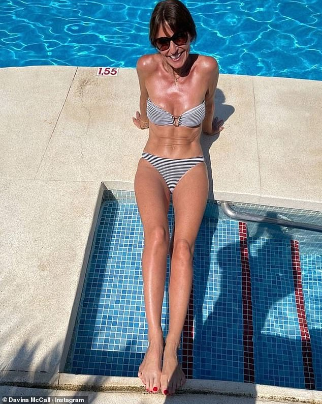 'Busy at work':Davina McCall, 53, looked nothing short of sensational as she took to Instagram to flaunt her flawless physiquein a strapless blue and white striped bikini on Saturday