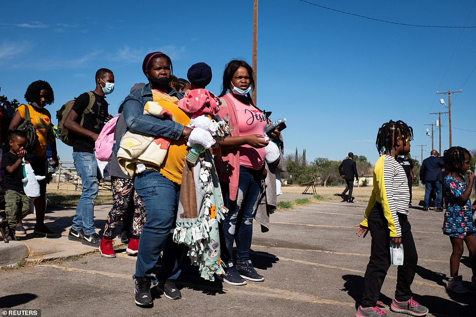 Migrants wait in line to board a bus to Houston from Val Verde Border Humanitarian Coalition in Del Rio, Texas, on Friday